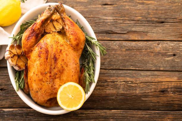geheel gebraden kip met citroen en rozemarijn op een zwarte plaat. rustieke stijl. kerst concept. kerst turkije. - geheel stockfoto's en -beelden