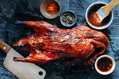 Whole roasted duck in marinade on stone background