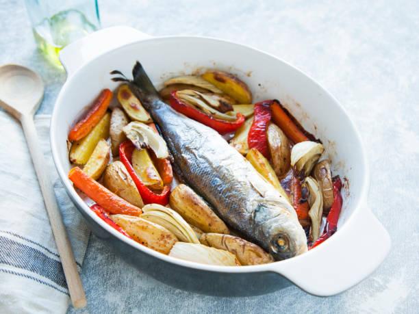 ganze fisch gekocht in kasserolle mit gemüse (paprika, karotten, kartoffeln, fenchel) auf grau-blauen hintergrund. - fenchelauflauf stock-fotos und bilder