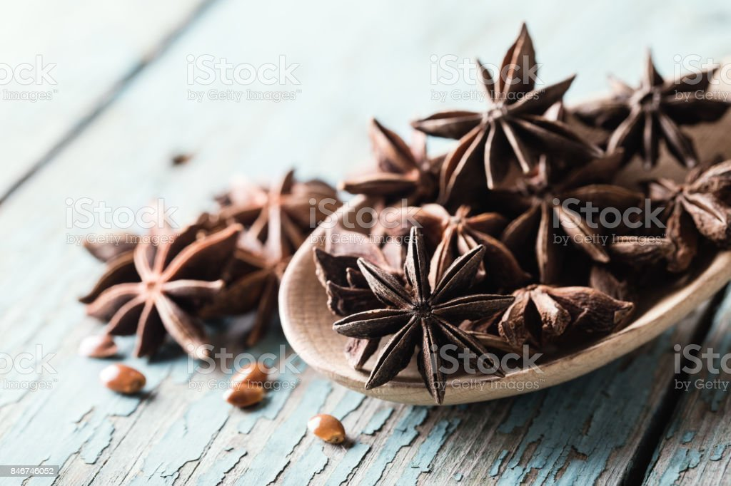 Whole star anise in a spoon on blue wooden background, close-up shot stock photo