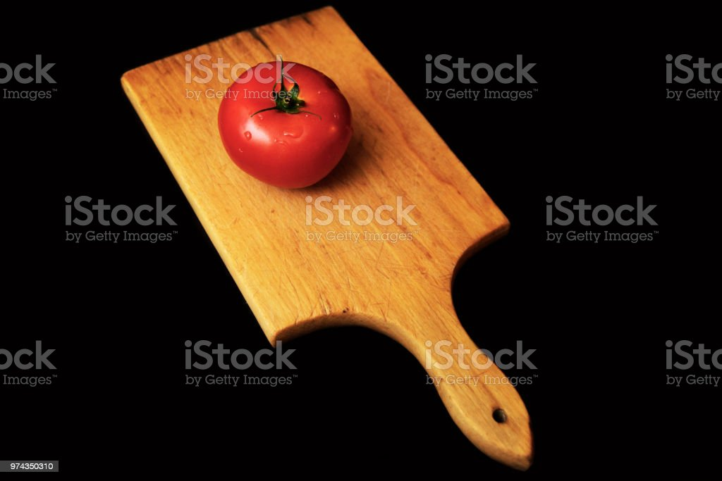 Whole tomato on cooking table stock photo