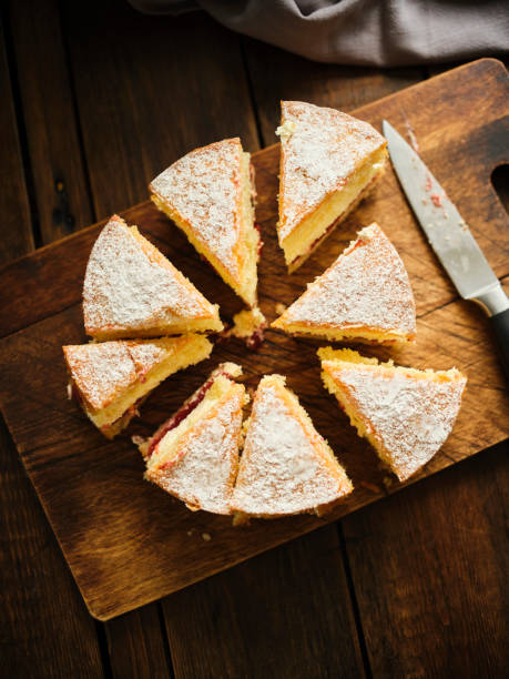a whole victoria sponge cake from above sliced into rough portions against a dark wood chopping board. - cake stock pictures, royalty-free photos & images