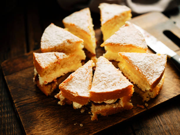 A whole Victoria Sponge cake sliced into rough portions against a dark wood chopping board.