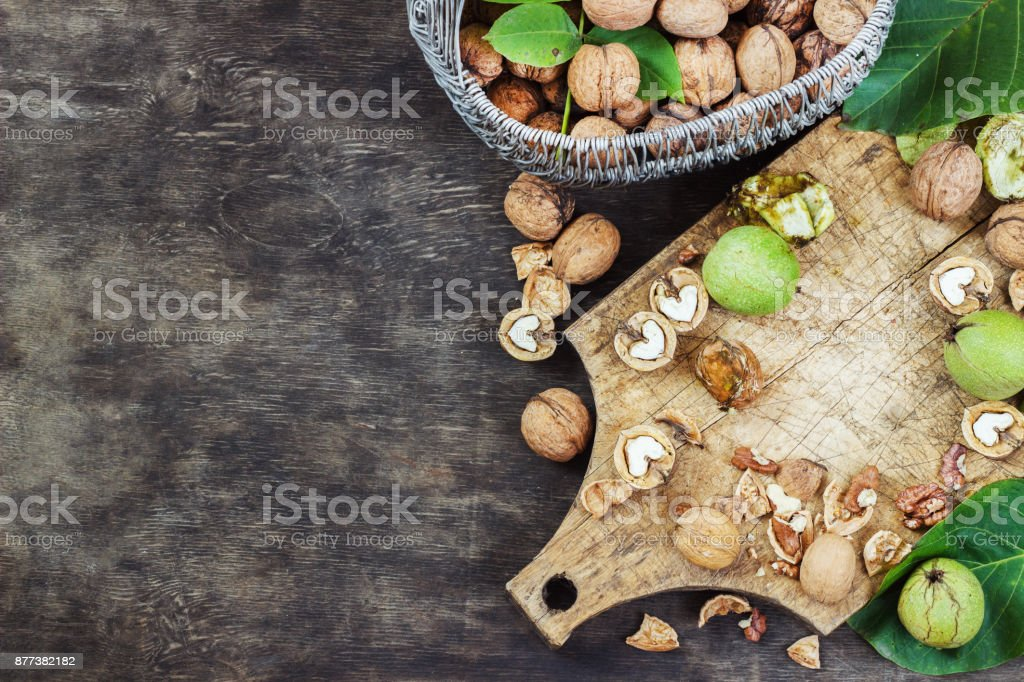 Whole Walnuts and Cleared Black Wooden Background Top view Healthy concept stock photo