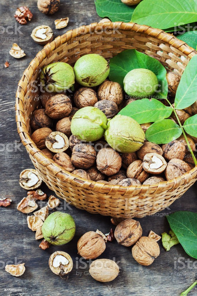 Whole Walnuts and Cleared in the basket Black Wooden Background Top view Healthy concept stock photo