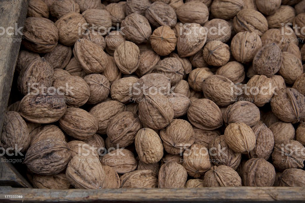 whole walnuts in wooden crate at farmers market royalty-free stock photo