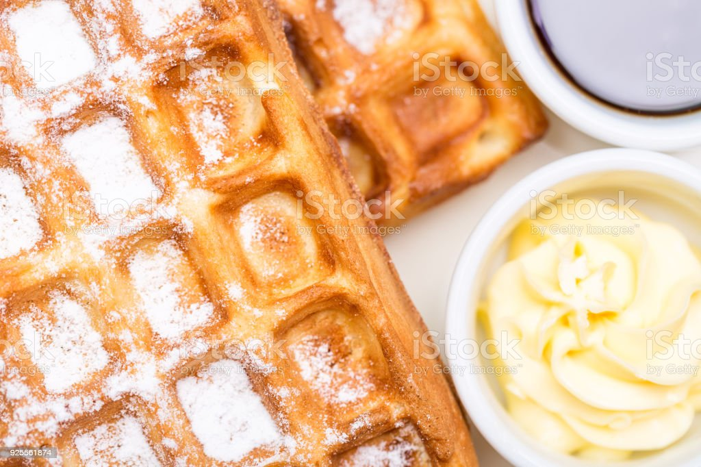 Whole wheat Belgium waffles on plate with butter and maple sauce. Selective focus stock photo
