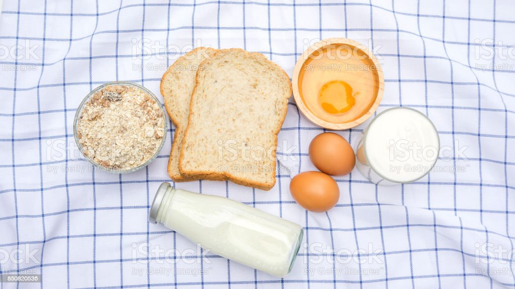 Whole wheat bread, oat, chicken egg, yogurt and milk on a table. stock photo
