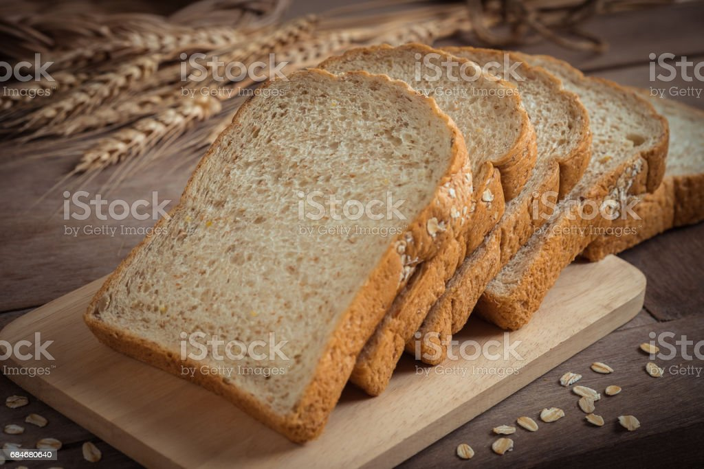 Whole wheat bread on wooden plate stock photo