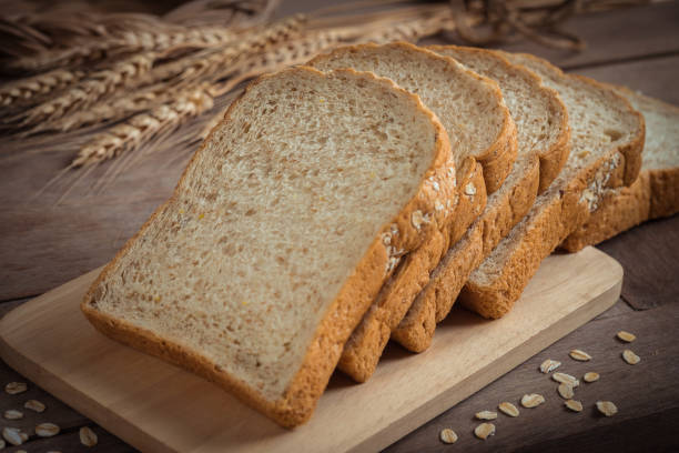 Whole wheat bread on wooden plate Whole wheat bread on wooden plate whole wheat stock pictures, royalty-free photos & images