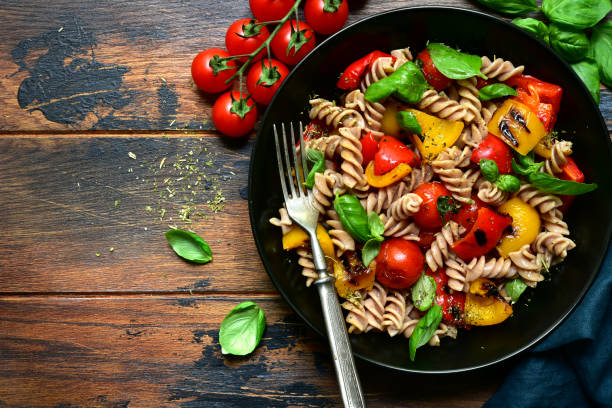 Whole wheat fusilli pasta with grilled vegetables Whole wheat fusilli pasta with grilled vegetables in a black bowl on a wooden background. Top view with copy space. fusilli stock pictures, royalty-free photos & images