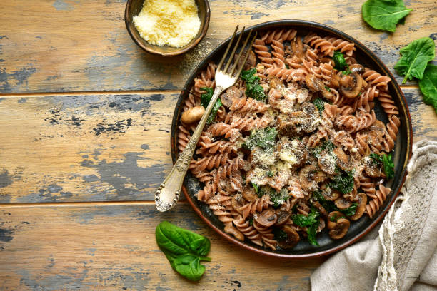 Whole wheat fusilli pasta with mushroom and spinach Whole wheat fusilli pasta with mushroom and spinach on a dark plate over old rustic wooden background.Top view with copy space. spelt stock pictures, royalty-free photos & images