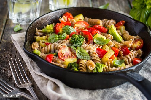 Whole wheat pasta  with vegetables on cast iron pan