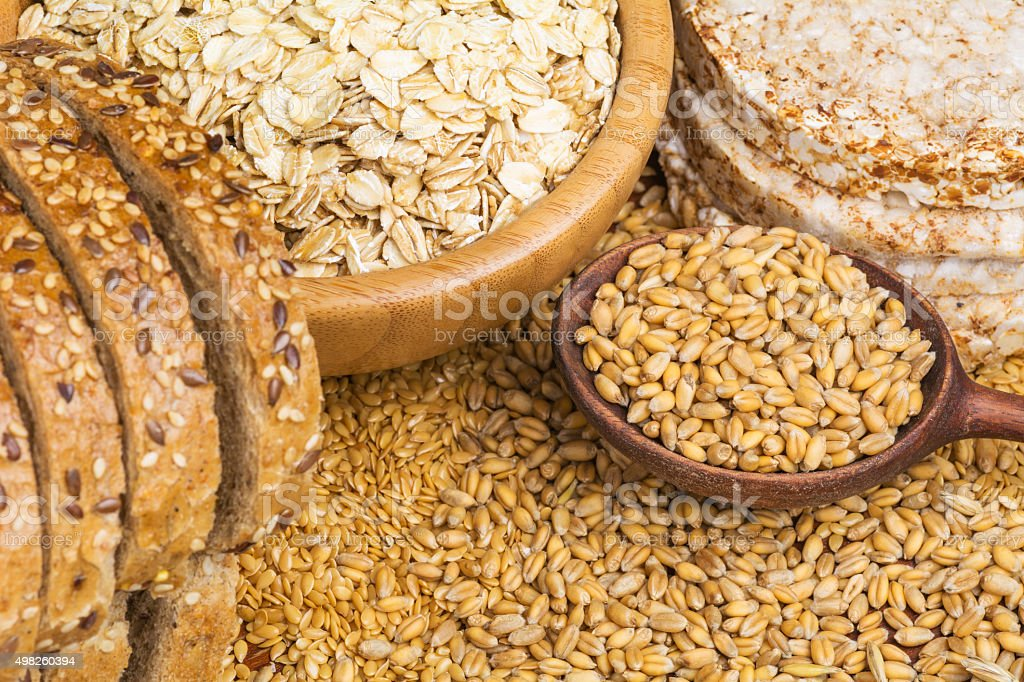 Whole wheat grains, bread, oats and oat cakes stock photo