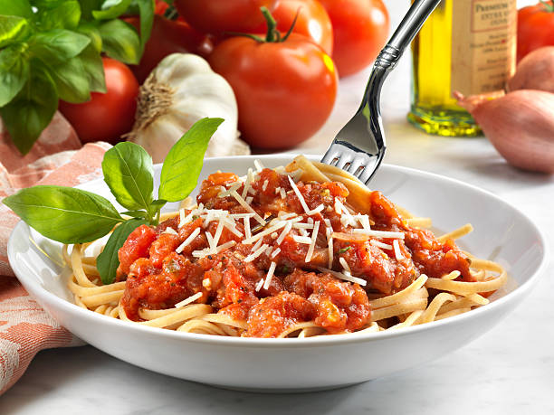 Whole Wheat Linguini with Tomato Sauce, Vegetarian Healthy meal of  whole wheat linguini with fresh chunky tomato sauce garnished with basil and parmesan cheese.  Vegetarian meal. burwellphotography stock pictures, royalty-free photos & images