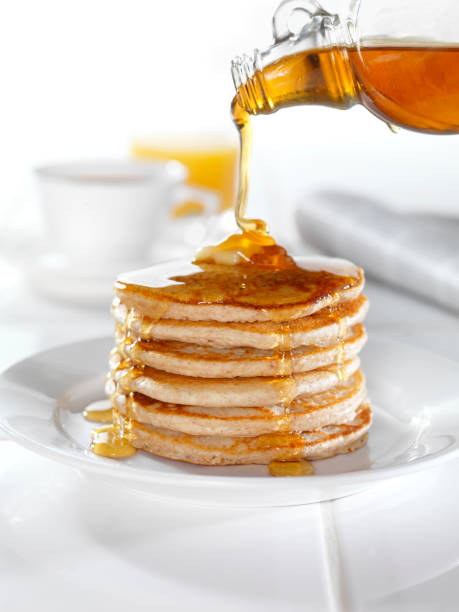 whole wheat pancakes with maple syrup - maple syrup stock photos and pictures