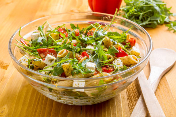Whole Wheat Pasta Salad with Fresh Arugula, Mozzarella, Roasted Red Bell Peppers and Pesto Sauce stock photo
