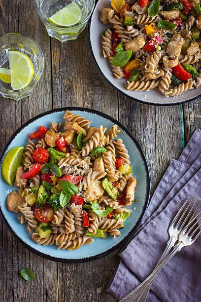 vollkorn-nudeln mit hühnchen und gemüse - gesunde huhn pasta stock-fotos und bilder