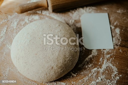 istock Whole wheat pizza dough shaped into ball on floured wooden background 920549904