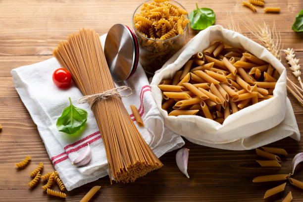Whole wheat spaghetti and penne on wooden table stock photo