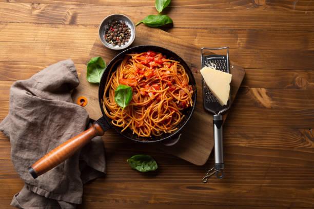 Whole wheat spaghetti in pan with tomato sauce stock photo