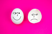 istock Whole White egg with smile and broken egg with Sad or Negative emotion on the pink background. Copy space. Minimalist, original and creative photo. Beautiful wallpaper. Different emotion. 1320619521