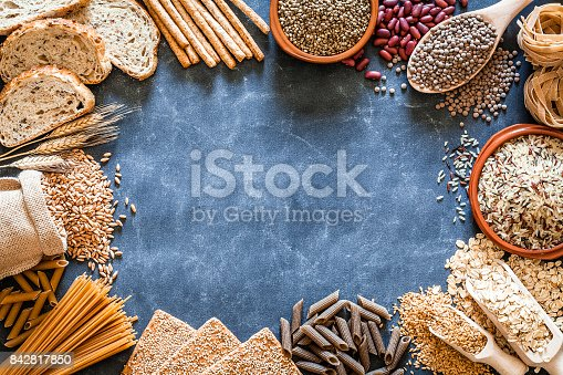 Top view of a dark slate table with wholegrain and cereals placed all around the border making a frame and leaving useful copy space for text and/or logo. This type of food is rich of fiber and is ideal for dieting. The composition includes wholegrain sliced bread, various kinds of wholegrain pasta, wholegrain crackers, breadstick, oat flakes, beans, brown rice, spelt and flax seeds. Predominant color is brown. Low key DSRL studio photo taken with Canon EOS 5D Mk II and Canon EF 100mm f/2.8L Macro IS USM
