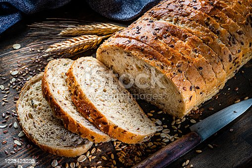 Healthy food: wholegrain and seeds sliced bread shot on rustic wooden table. Predominant color is brown. High resolution 42Mp studio digital capture taken with Sony A7rII and Sony FE 90mm f2.8 macro G OSS lens