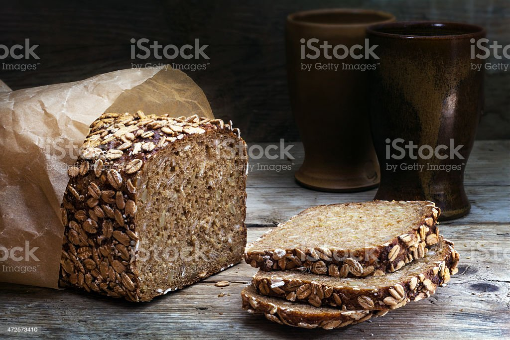 wholegrain bread with seeds on weathered wood, dark background stock photo