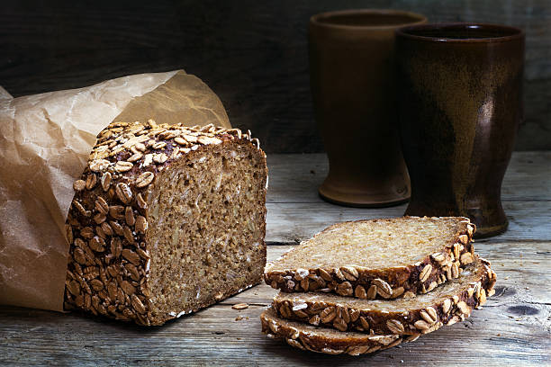wholegrain bread with seeds on weathered wood, dark background wholegrain rye bread with seeds on a weathered wooden board, rustic earthenware in the dark background spelt stock pictures, royalty-free photos & images