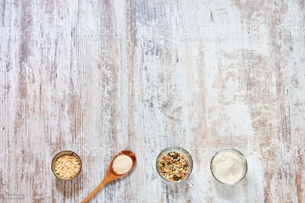 Wholegrain flour, grains and seeds, oat flakes, wooden spoon on a light rustic table. stock photo