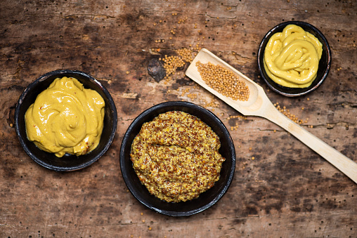 Wholegrain mustard in a bowl on a table top view