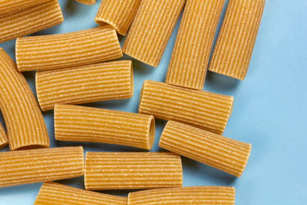 Wholegrain Rigatoni Uncooked whole grain rigatoni on a blue background rigatoni stock pictures, royalty-free photos & images
