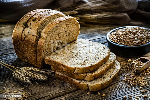 Wholegrain sliced bread shot on rustic wooden table. A bowl filled with wholegrain spelt is at the right beside the sliced bread. XXXL 42Mp studio photo taken with SONY A7rII and Zeiss Batis 40mm F2.0 CF