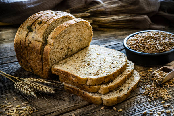 Wholegrain sliced bread Wholegrain sliced bread shot on rustic wooden table. A bowl filled with wholegrain spelt is at the right beside the sliced bread. XXXL 42Mp studio photo taken with SONY A7rII and Zeiss Batis 40mm F2.0 CF bread stock pictures, royalty-free photos & images