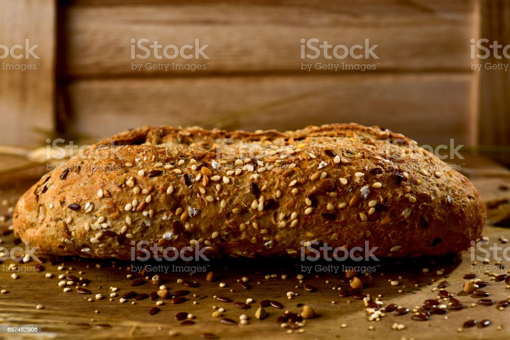 wholemeal bread roll topped with different seeds stock photo
