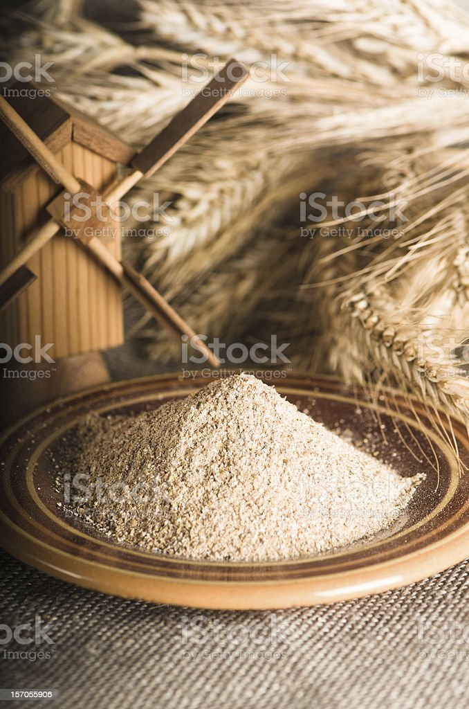 Wholemeal flour and wheat on cloth sack, close-up stock photo