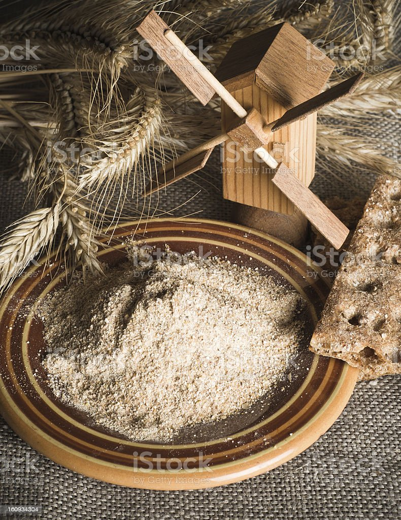 Wholemeal flour and wheat on cloth sack, close-up royalty-free stock photo
