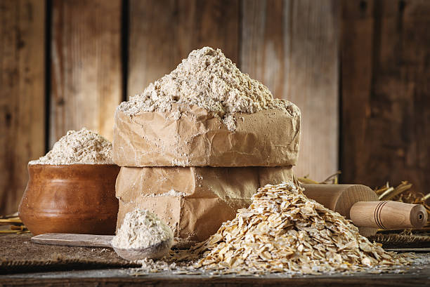 Wholemeal Oat flour and oat flakes, rolling pin, spoon stock photo