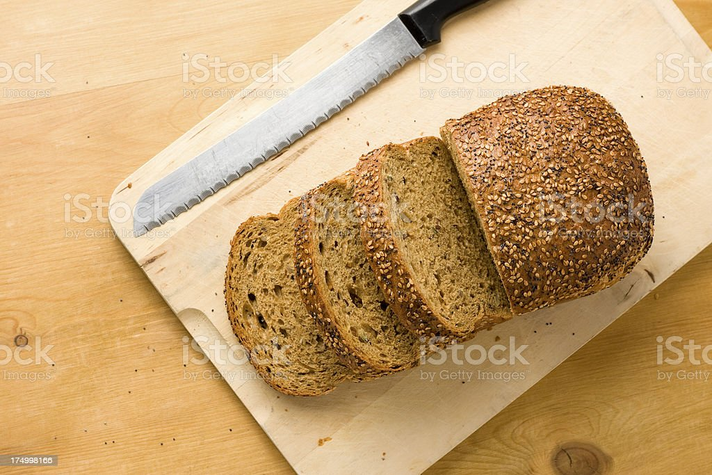 Wholemeal seeded brown bread loaf on a chopping board stock photo