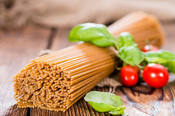 Wholemeal Spaghetti Wholemeal Spaghetti (close-up shot) on an old wooden table whole wheat stock pictures, royalty-free photos & images