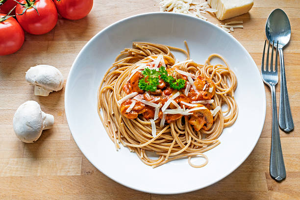 wholemeal spaghetti with sauce of tomatoes, mushrooms and parmes rustic wholemeal spaghetti with sauce of tomatoes, mushrooms and Parmesan cheese on a wooden table whole wheat stock pictures, royalty-free photos & images