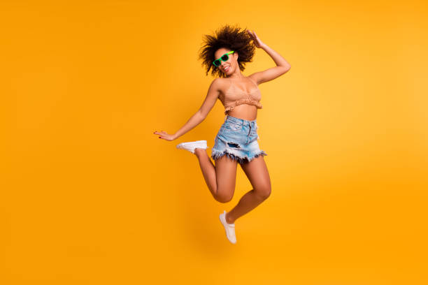 Whoo! I go crazy! Dreams come true! Full-length full-size photo of cheerful cute relaxed full of energy positive afro woman with curly short brown hair casual clothed, isolated on yellow background stock photo