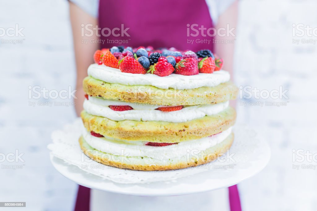 Whoopie cake on the plate with fresh berries, women's hands holding. stock photo
