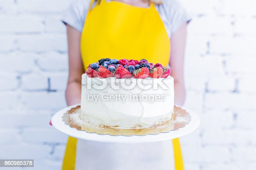 istock Whoopie cake on the plate with fresh berries, women's hands holding. 860985378