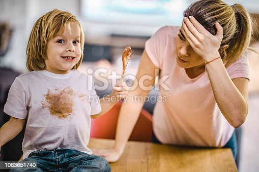 Small boy stained himself with chocolate while his mother is in disbelief.