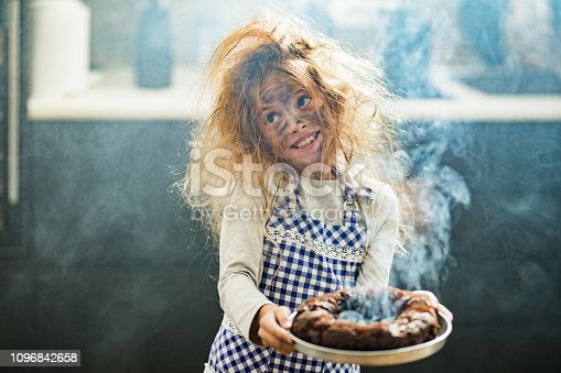 Happy little girl with messy hair holding burnt the cake in the kitchen.