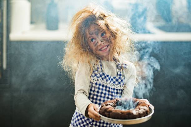 Whops, I have burnt the cake! Happy little girl with messy hair holding burnt the cake in the kitchen. mistake stock pictures, royalty-free photos & images