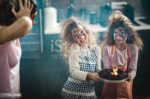 Small girls with messy hair and face baked a burnt cake while their mother is in shock.