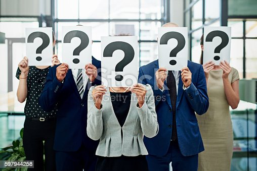 Cropped shot of a group of unidentifiable businesspeople holding placards with question marks on them in front of their faces